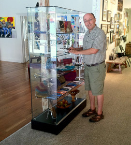 SAM Board President, Ernie Wasson adds artwork to the new display case funded by a grant from the McConnell Fund of the Shasta Regional Community Foundation.
