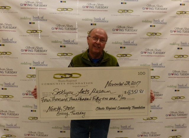 SAM's President Ernie Wasson displays the check received from Giving Tuesday donations.
